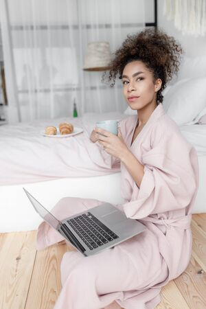 Beautiful young woman with laptop holding cup of coffee Reklamní fotografie
