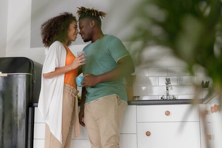 Beautiful young couple in love standing in the kitchen