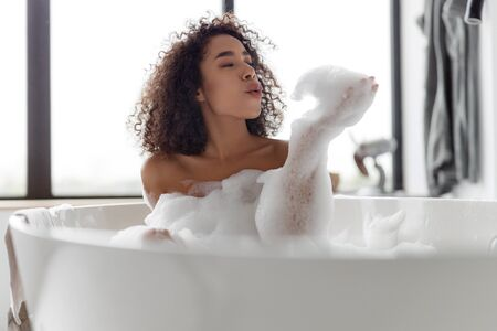 Charming Afro American lady relaxing in bathtub