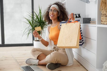 Charming lady holding gold card and shopping bags