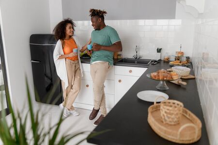 Cheerful young couple standing in the kitchen
