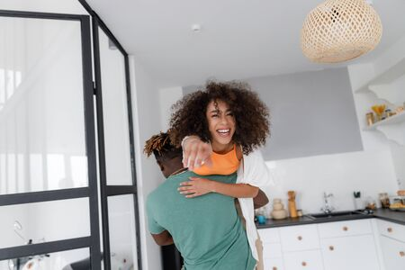 Afro American guy carrying cheerful lady on his shoulder Stock fotó