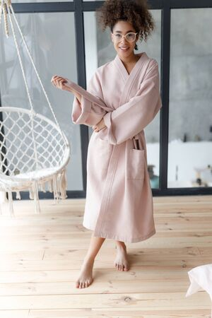 Cheerful young woman holding belt of her bathrobe