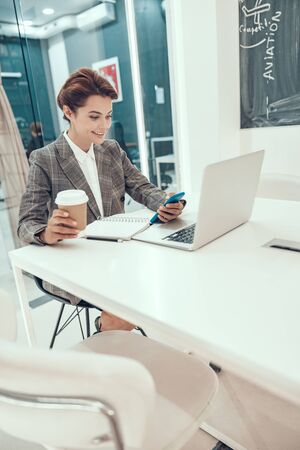 Happy entrepreneur with coffee and gadgets stock photo