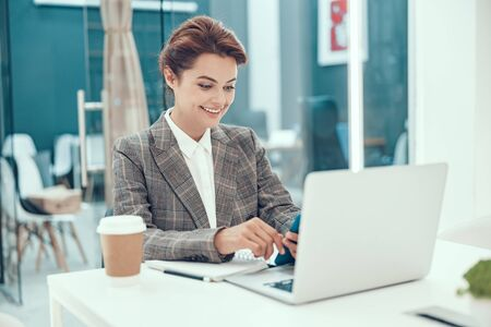 Happy young business woman with laptop stock photo