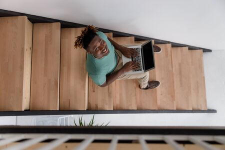 Cheerful Afro American man using laptop at home