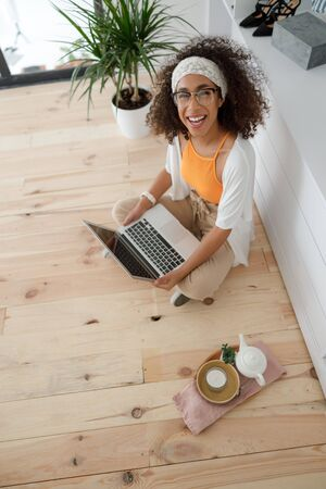 Cheerful Afro American lady using notebook at home
