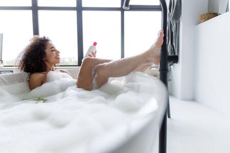 Joyful young lady lying in bathtub and holding bottle of shampoo