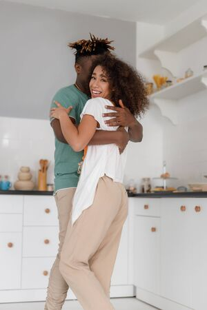 Happy loving couple hugging in kitchen at home Stock fotó