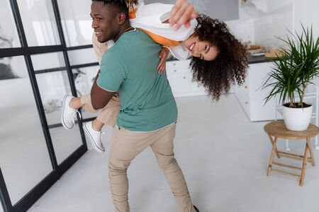 Cheerful man having fun with his girlfriend at home