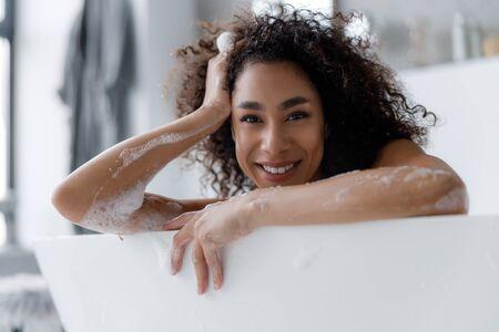 Beautiful Afro American lady relaxing in bath Stock fotó