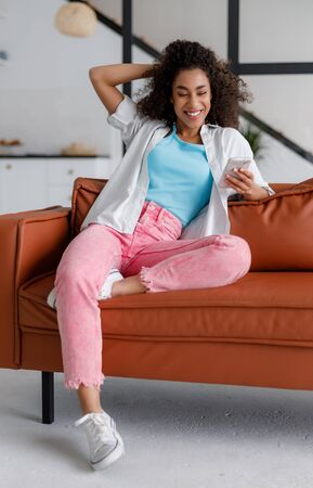 Joyful Afro American lady using smartphone at home