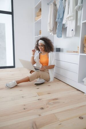 Cheerful Afro American lady using laptop at home