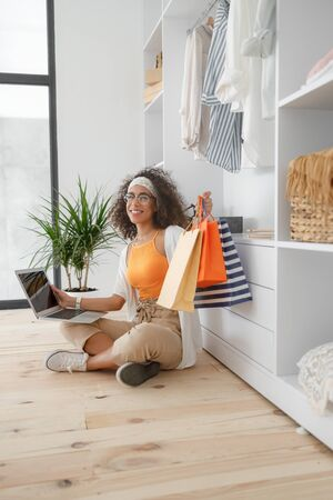 Smiling lady with laptop holding shopping bags
