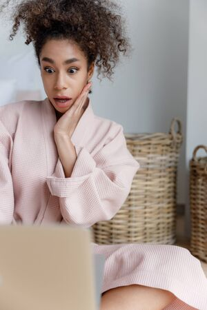 Astonished Afro American lady using laptop at home