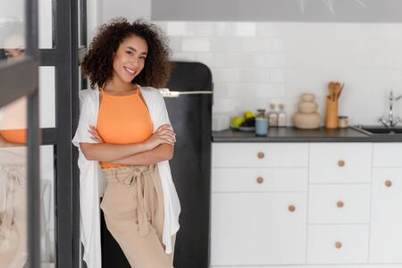 Cheerful Afro American lady standing in the kitchen