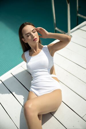 Beautiful young woman sunbathing by the pool