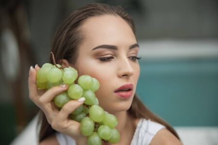 Pretty woman with grape is looking away 版權商用圖片