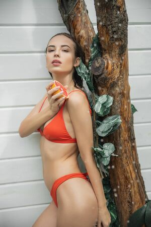 Cute young lady is posing with grapefruit