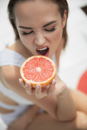 Pretty young lady going to bite a grapefruit