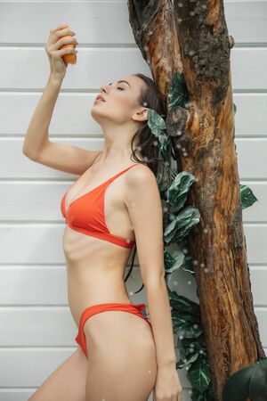Cute lady in swimsuit posing with grapefruit 版權商用圖片