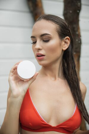 Pretty lady with wet hair holding cream