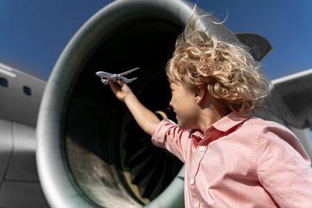 Little boy is playing near big plane