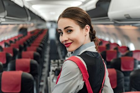 Pretty young air hostess is looking at camera