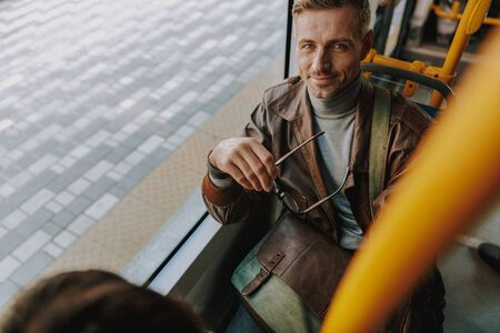 Handsome man sitting by the window in a tram