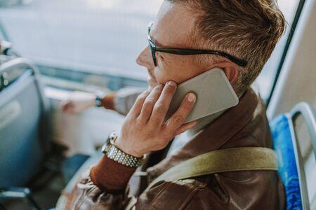 Handsome man talking on cellphone in public transport