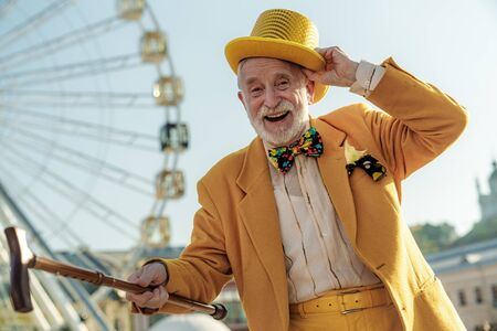 Happy aged man in coloured suit in amusement park