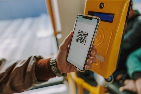Man using smartphone and QR code to pay tram fare