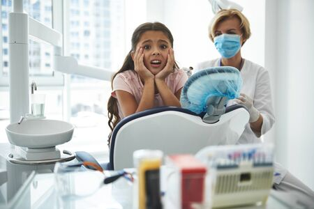 Young girl is feeling fear at dentist
