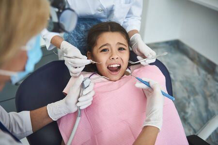 Teenage lady is feeling fear at dentist Stock Photo