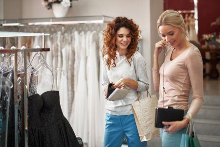 Two young ladies choosing clutch bag in shop