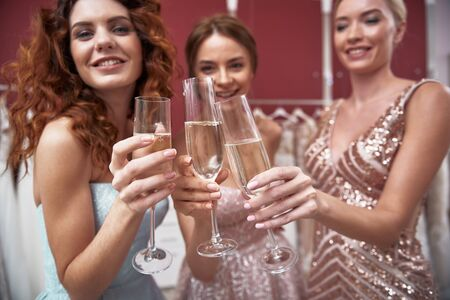 Young happy ladies clanging of champagne glasses