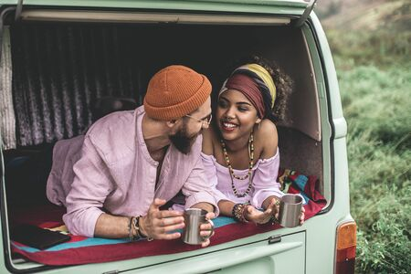 Hippie couple resting in retro van with cup of tea