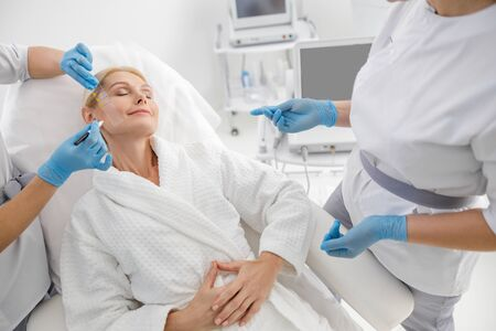 Specialists preparing female patient for an ultrasonic lift Zdjęcie Seryjne