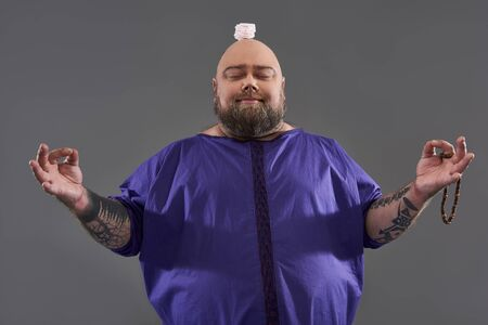 Funny man meditating with marshmallow souffle on his bold head