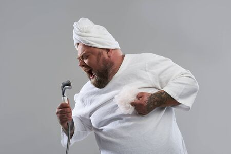 Waist up of fat man singing into the shower head