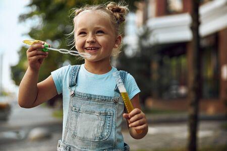 Happy kid enjoying blowing bubbles stock photo