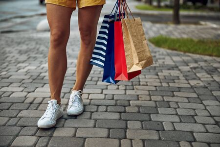 Cropped photo of a lady in the street with colorful paper bags