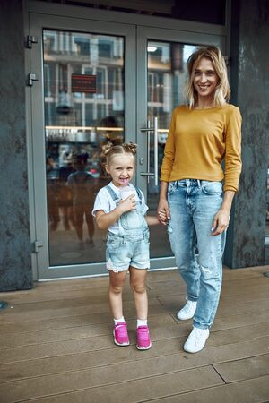 Mother and daughter standing outside the cafe stock photo