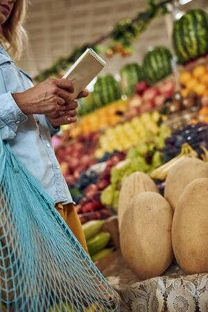 Cropped photo of a woman with a mesh shopping bag and a notebook at the market