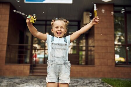 Excited child outdoors with soap bubbles