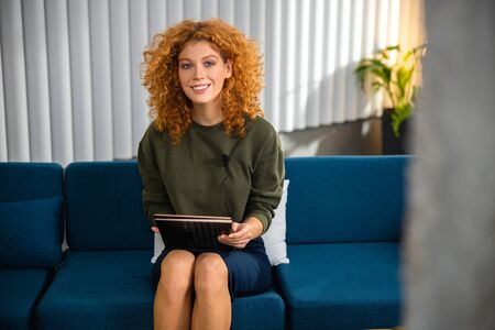 Cheerful woman holding touchpad indoors stock photo