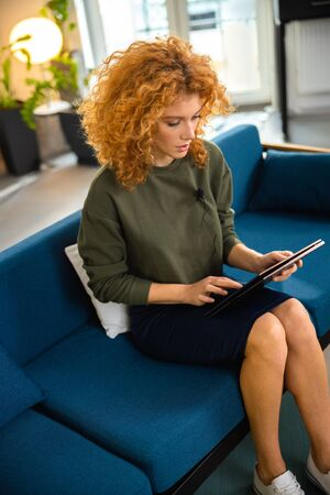 Woman working on laptop on couch stock photo