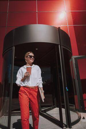 Beautiful stylish woman walking out of business center