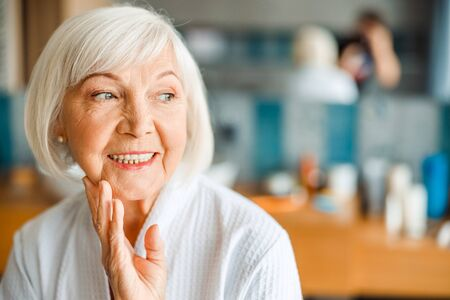 Cheerful old woman looking away and smiling