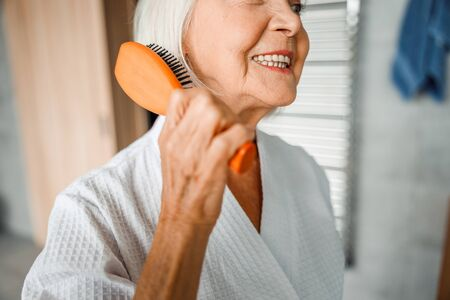 Cheerful elderly woman brushing hair and smiling